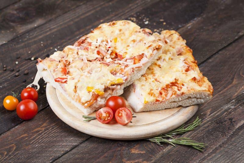 Hemlagad pizza p? en m?rk tabell tjock pizza som hemma lagas mat fotografering för bildbyråer