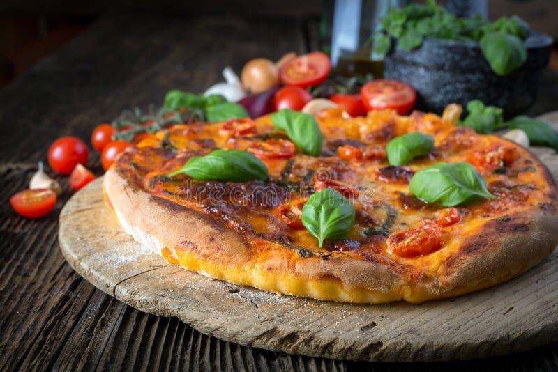 hemlagad pizzamargherita med mozzarellaen, basilika och tomater royaltyfri foto