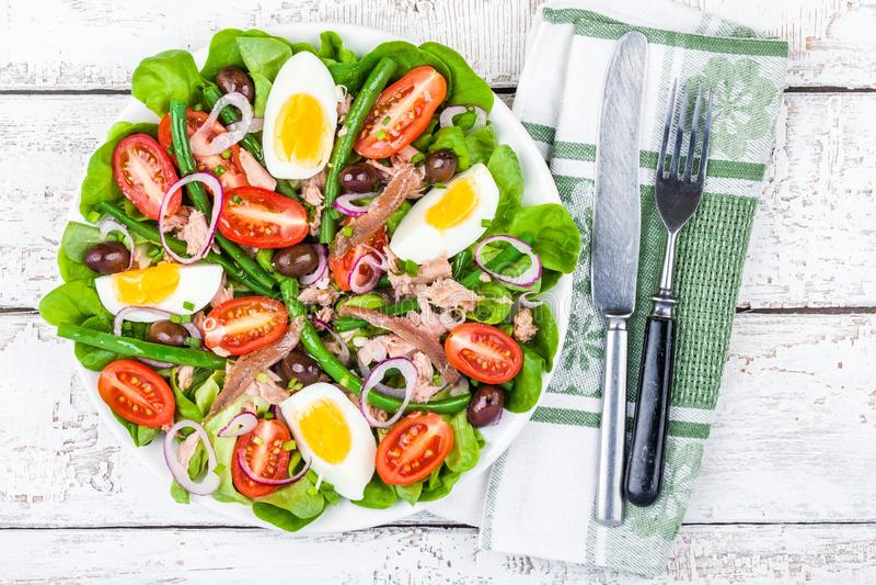 Hemlagad salladnicoise med tonfisk, ansjovisar, tomater royaltyfri fotografi