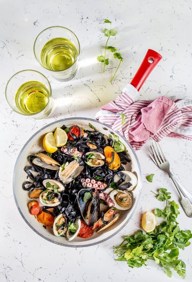 Hemlagad spagetti för skaldjursvartpasta med vongole för musslamusslabläckfisk i panna med vitt vin på marmorerad bakgrund arkivfoto