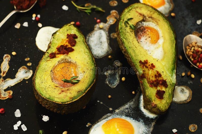 Hemlagad startknapp - bakad avokado med vaktelägget och kryddor arkivfoto