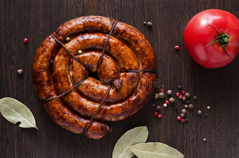 Hemlagad stekt spiral korv som göras från kött med kryddor på den mörka tabellbakgrunden arkivfoto