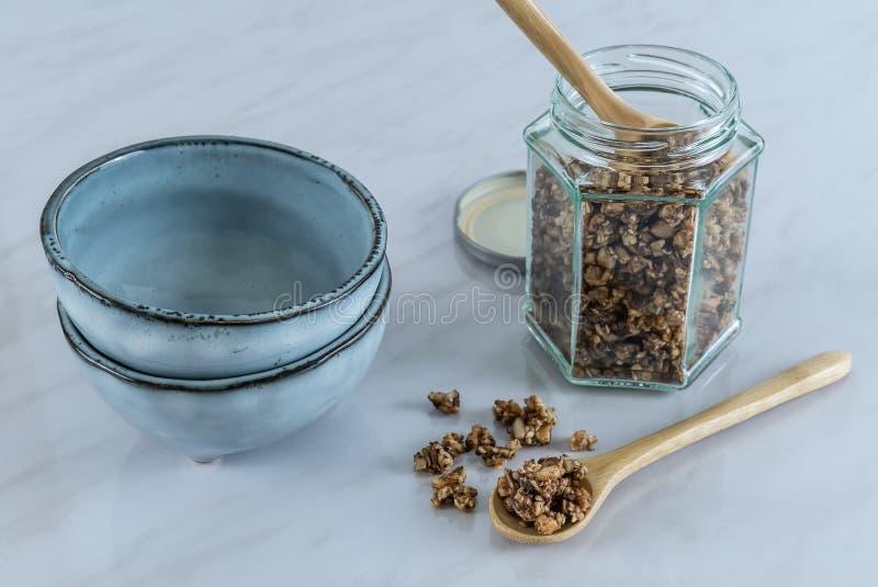 Hemlagad sund och näringsrik frukostgranola i en exponeringsglaskrus med träskeden och blåa keramiska bunkar på marmor royaltyfri fotografi