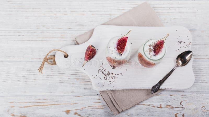 Hemlagad sund yoghurt i exponeringsglaskrus med fikonträd och chiafrö arkivfoton