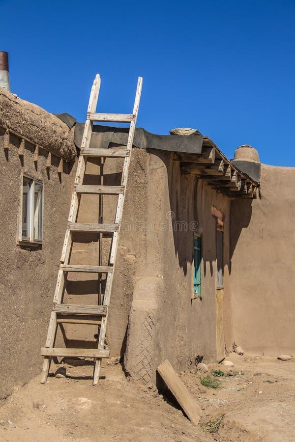 Hemlagad trästege mot sida av huset för gyttjaAdobepueblo var tjärapapper är det pålagda taket - med dramatiska skuggor under arkivfoto