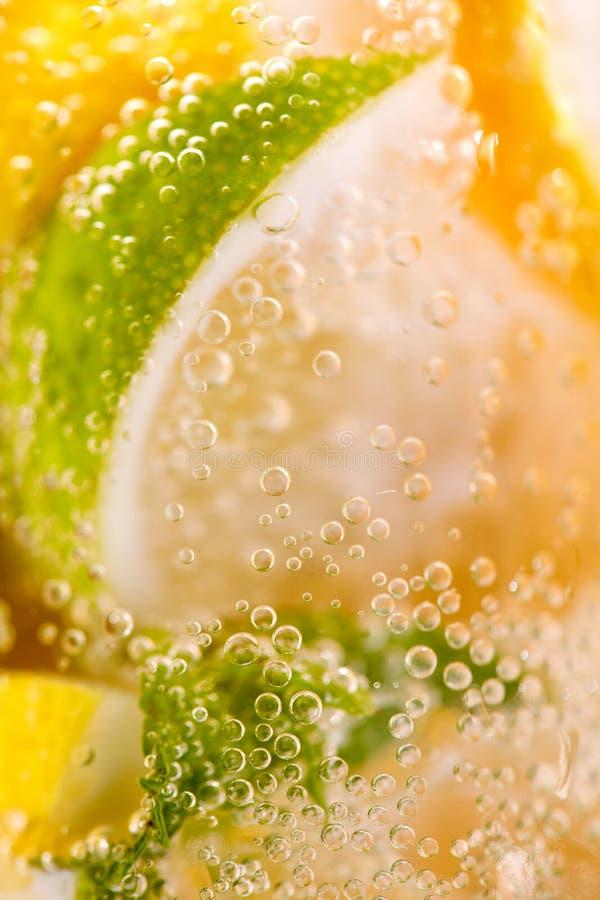 Hemlagad uppfriskande drink som g?ras fr?n citron- och limefruktskivor med bubblor Makrofoto av sund lemonad f?r sommar royaltyfri foto