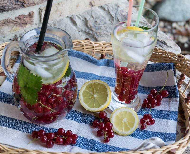 Hemlagad uppfriskande lemonad av den röda vinbäret med is och citronen arkivfoto