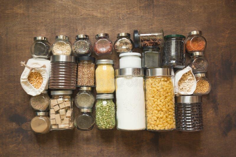Hemlagad uppsättning av wholegrain sädesslag, pasta, kryddor, kaffe, mjöl, socker på en trätabletop ovanf?r sikt arkivfoton