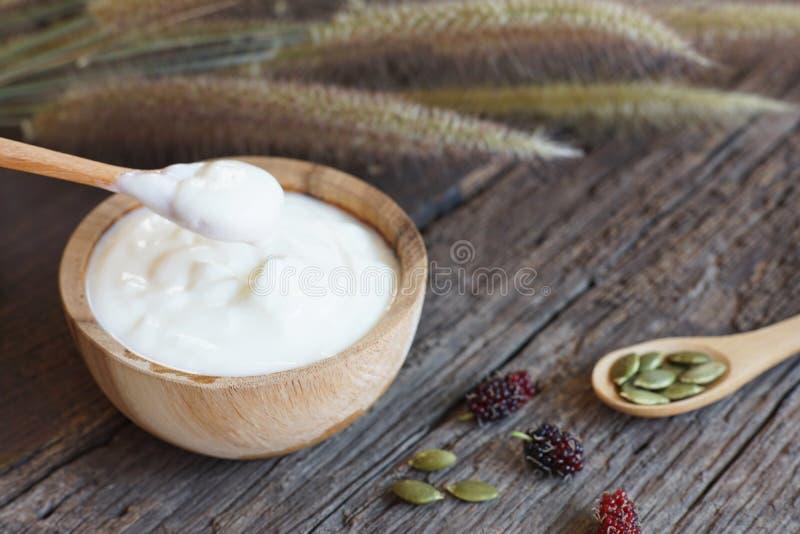 Hemlagad vanlig organisk yoghurt med ny bärfrukt och sädesslag i träbunke- och träsked på trätexturbakgrund arkivbild