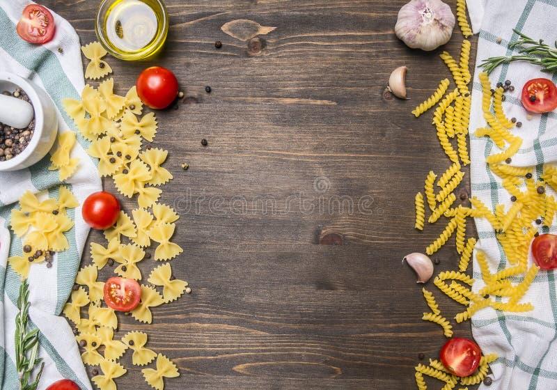 Hemlagad vegetarisk pasta som läggas ut på en trälantlig tabell med örter, köktorkduk, körsbärsröda tomater, gräns, ställe för te arkivbild