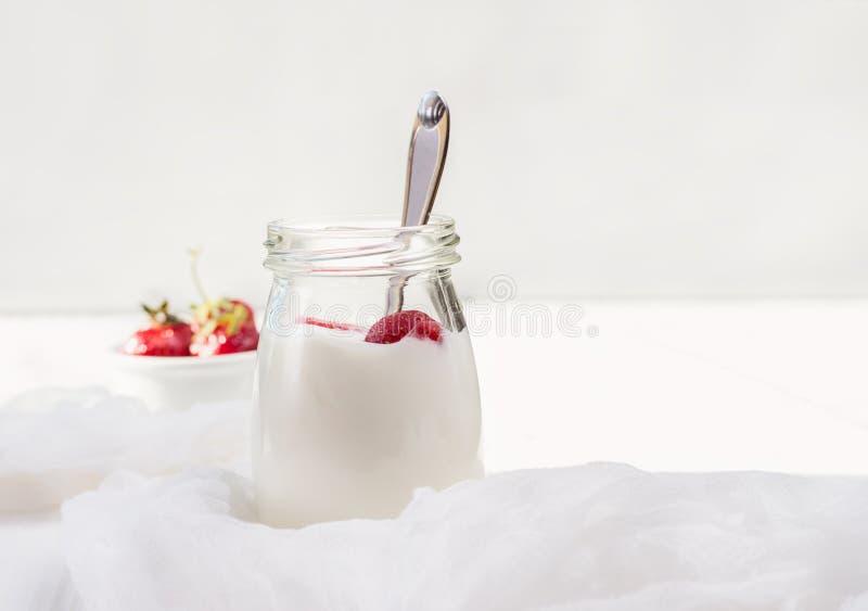 Hemlagad yoghurt med nya jordgubbar på en ljus träbakgrund arkivfoto