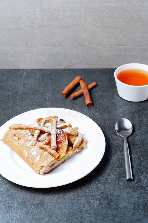 Hemlagade äppelpaj- och te- och cinnamonepinnar på mörk bakgrund arkivfoton