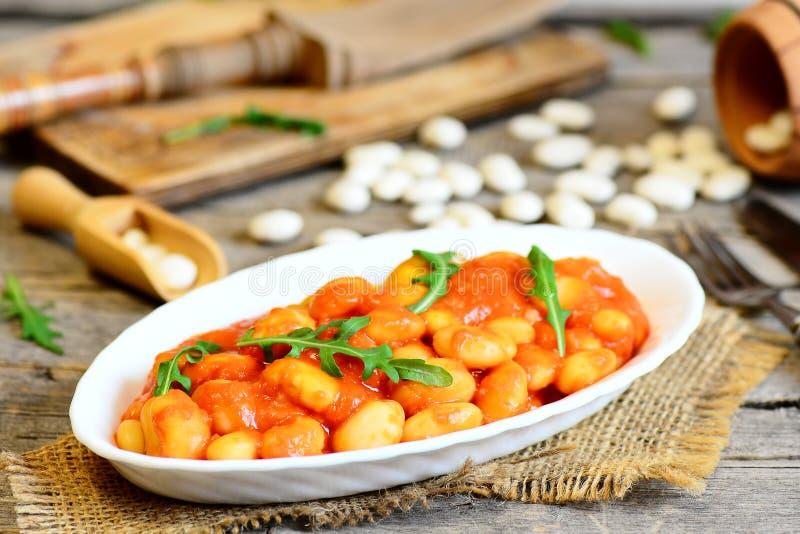 Hemlagade bönor låter småkoka på en platta och på den gamla trätabellen Vita bönor lät småkoka med morötter och tomatsås arkivfoton