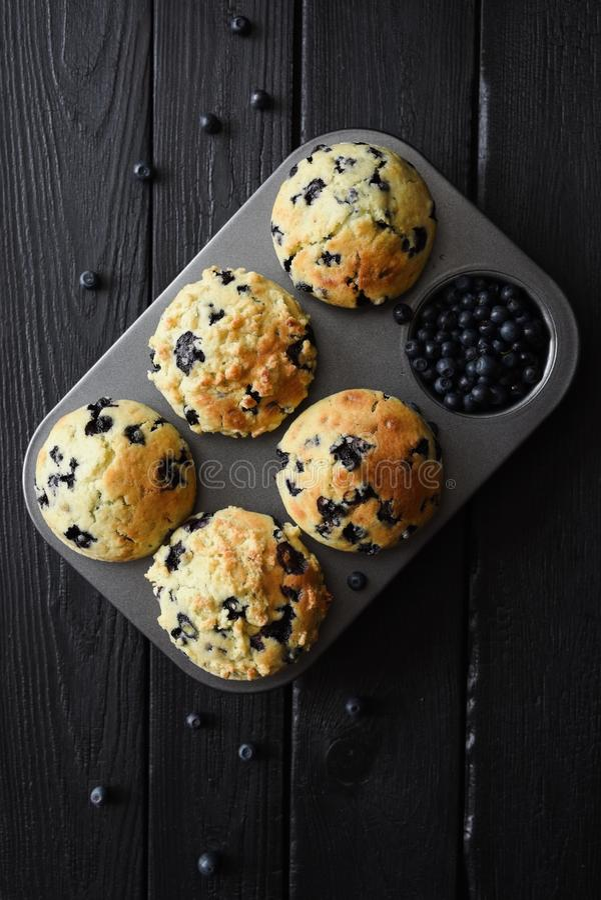 Hemlagade blåbärmuffin och rå blåbär på svart bakgrund med naturligt bästa sikt för tända arkivfoton