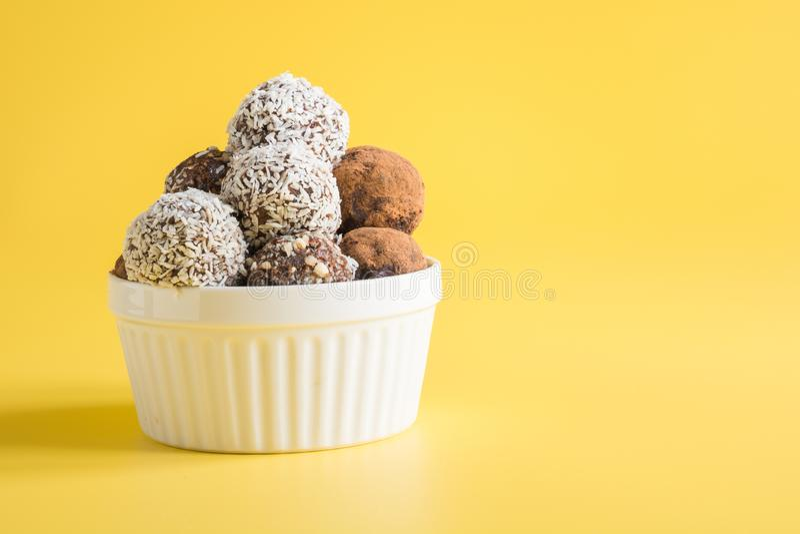 Hemlagade bollar för naturlig energi, strikt vegetarianchokladtryffel med kakao, kokosnöt på gul bakgrund Sund mat för barn, söts arkivfoton