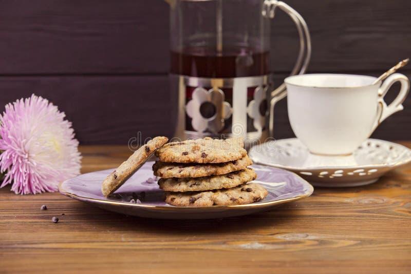 Hemlagade choklade kakor på ett härligt tefat, kokkärl av te, på en trämörk bakgrund royaltyfria foton
