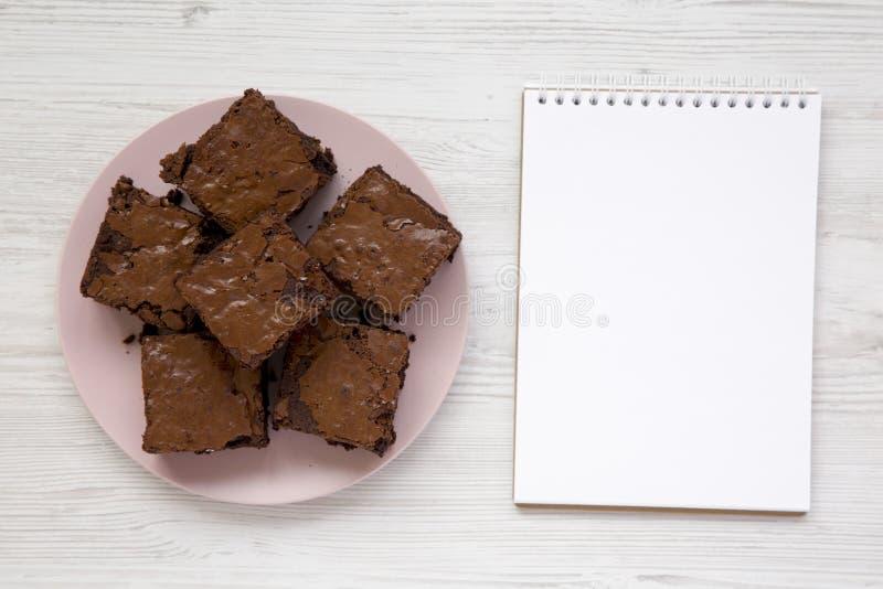 Hemlagade chokladnissen på en rosa platta, tom notepad, bästa sikt Lekmanna- l?genhet, ?ver huvudet, fr?n ?ver kopiera avst?nd arkivbild