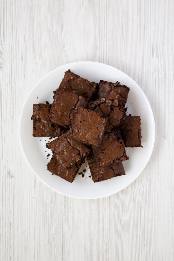 Hemlagade chokladnissen på en vit platta på en vit träbakgrund, bästa sikt Lekmanna- l?genhet, ?ver huvudet, fr?n ?ver closeup royaltyfria foton