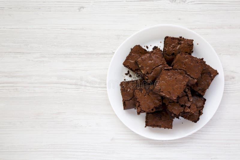 Hemlagade chokladnissen på en vit platta på en vit trätabell, bästa sikt Lekmanna- l?genhet, ?ver huvudet, fr?n ?ver kopiera avst arkivbild