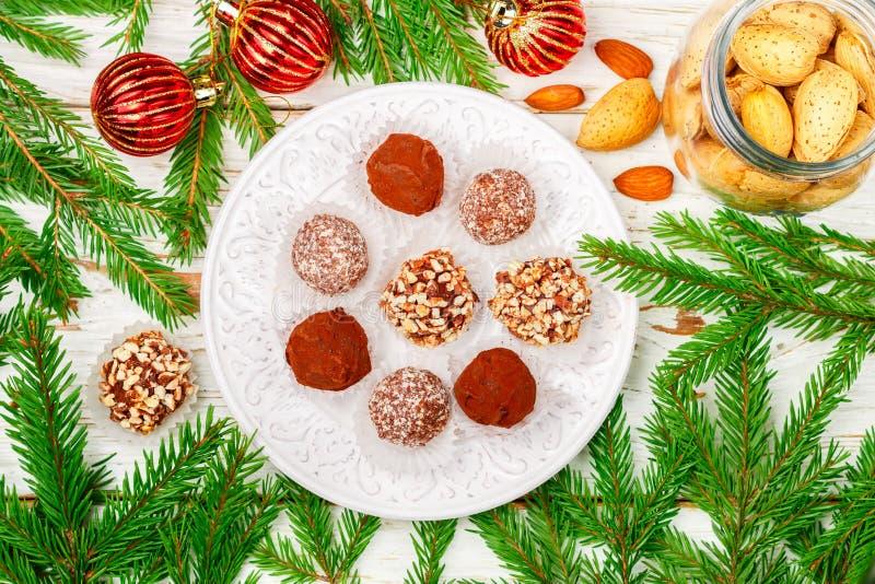 Hemlagade chokladtryfflar med mandlar, kokosnöten och kex panerar i en vit platta arkivfoton