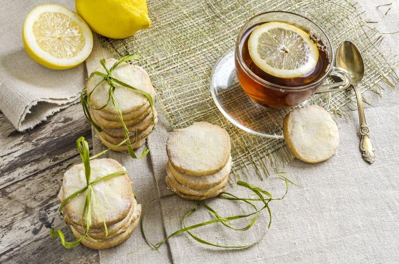 Hemlagade citronsockerkakor och kopp av varmt te på linnebordduk royaltyfria foton