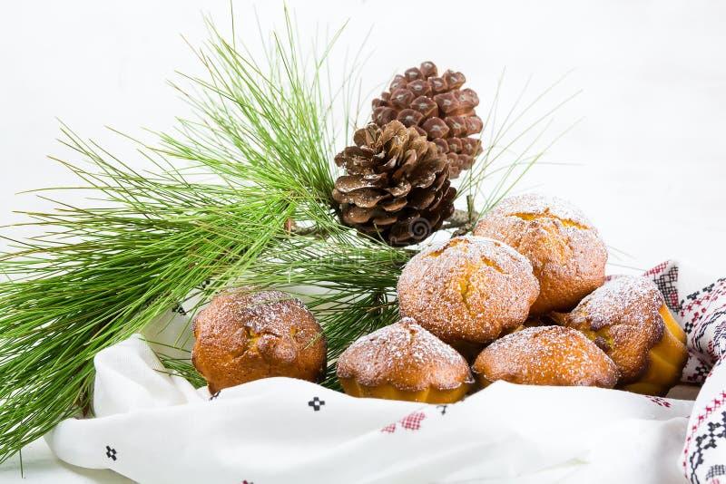 Hemlagade cristmas muffin, julmuffin och ny yaergarnering på den vita bakgrunden och att sörja filialer och kottar royaltyfri foto