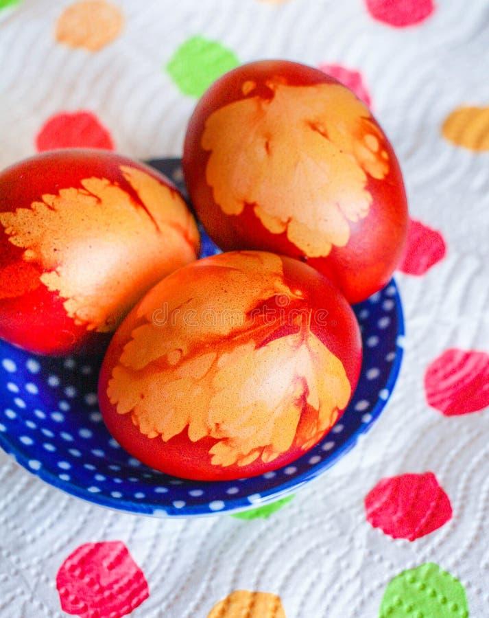 Hemlagade easter ägg på färgrik servett och en gullig blåttplatta royaltyfria foton