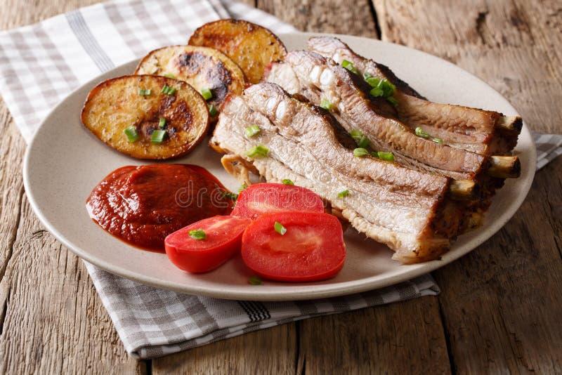 Hemlagade Fried Pork Ribs med potatisar på en platta horisontal arkivfoton