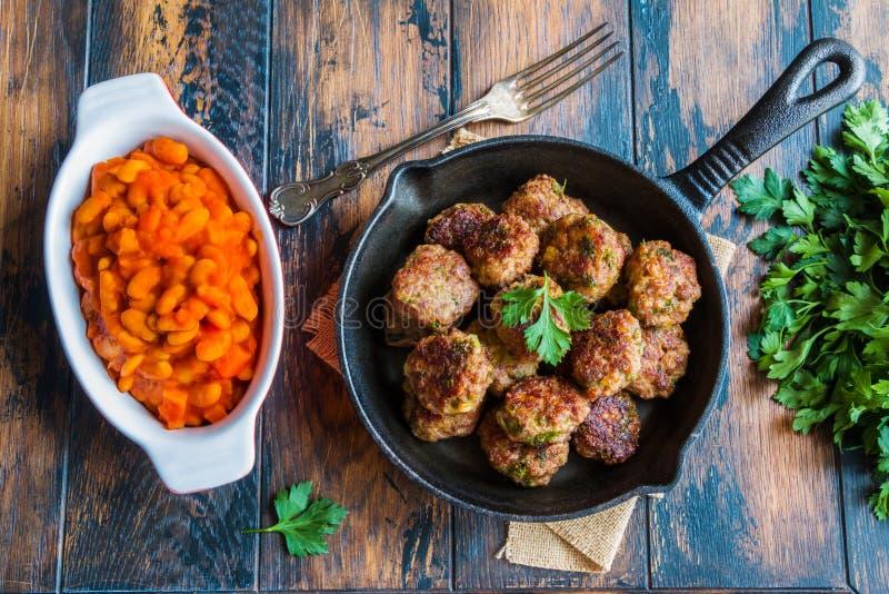 Hemlagade grillade nötköttköttbullar i järn- kastrull och bönor bakade i tomatsås i bakningmaträtt på trätabellen i kök royaltyfri bild