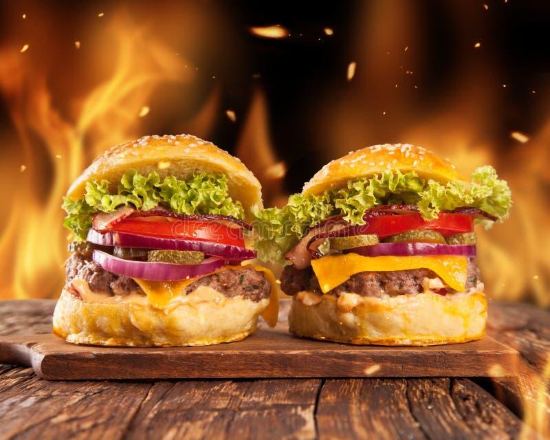 Hemlagade hamburgare med brand royaltyfri foto