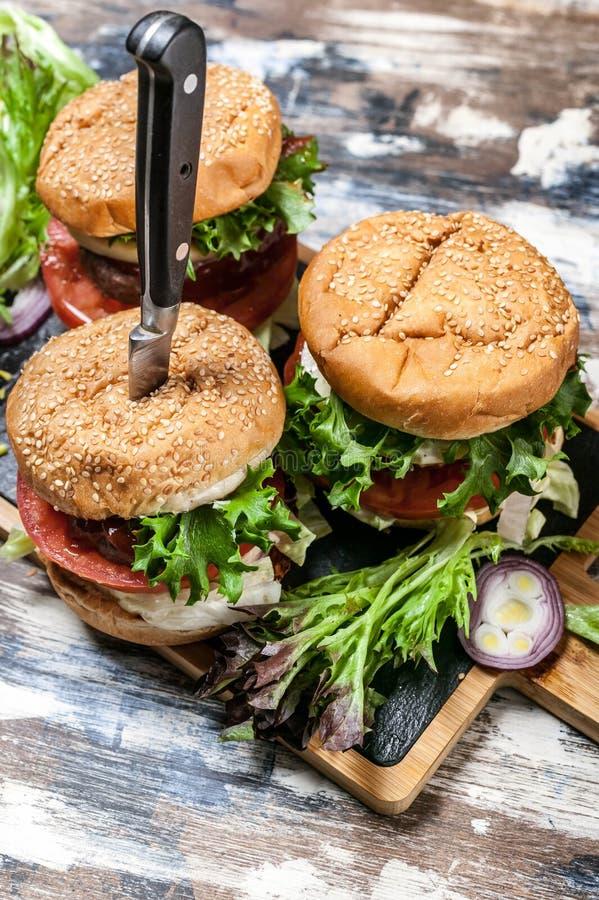 Hemlagade hamburgare med nötkött, tomater, grönsallat, ost och kryddig tomatsås på en skärbräda royaltyfri fotografi