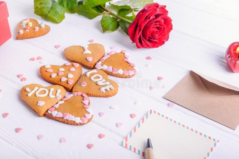 Hemlagade kakor i form av hjärta med älskar jag dig ord som gåvan för vän på dag för valentin` s Vit trätabell med att hälsa c fotografering för bildbyråer