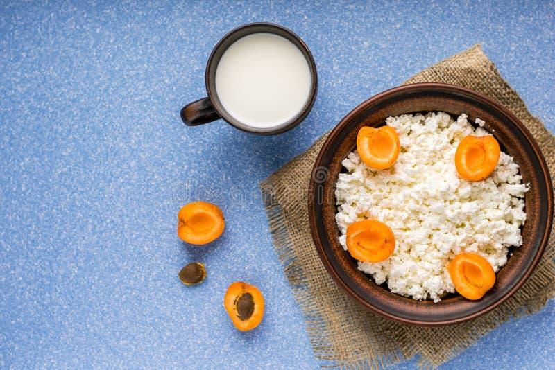 Hemlagade keso med nya aprikors i en bunke på en säck och trä rånar med mjölkar på en blå tabell Top besk?dar kopia arkivfoton