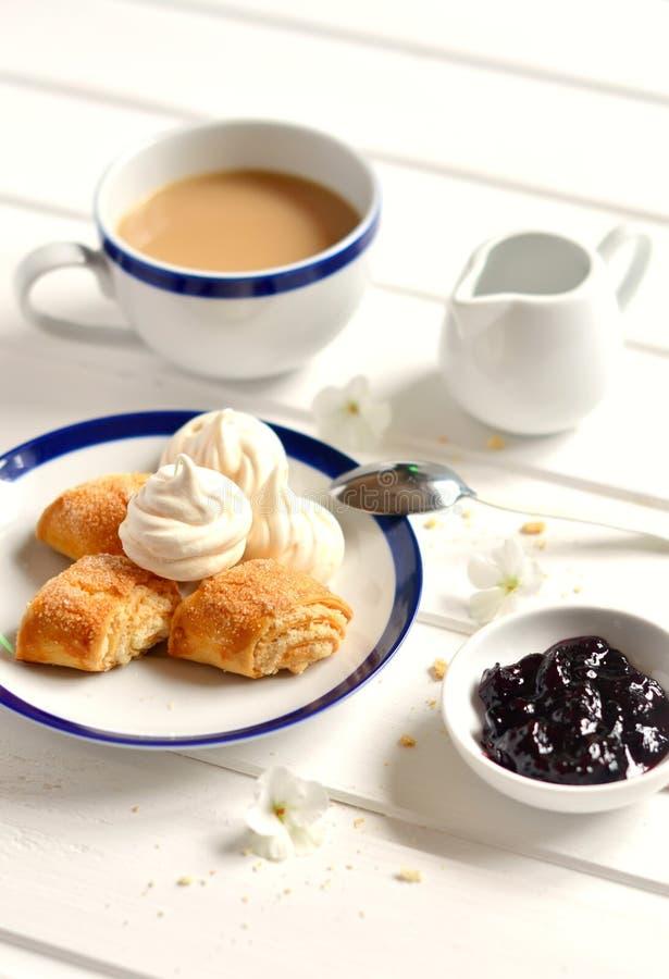 Hemlagade kex, marängar och te med mjölkar arkivbild