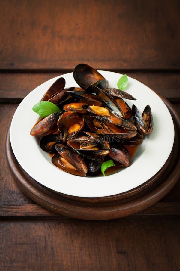 Hemlagade lagade mat musslor med vitlök, tomatsås, italienska örter, vitt vin och ny basilika i en platta royaltyfria foton