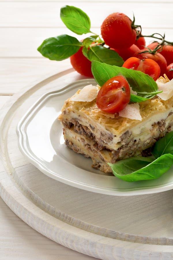 Hemlagade lasagner med bechamelsås dekorerade basilikasidor och körsbärsröda tomater arkivbild