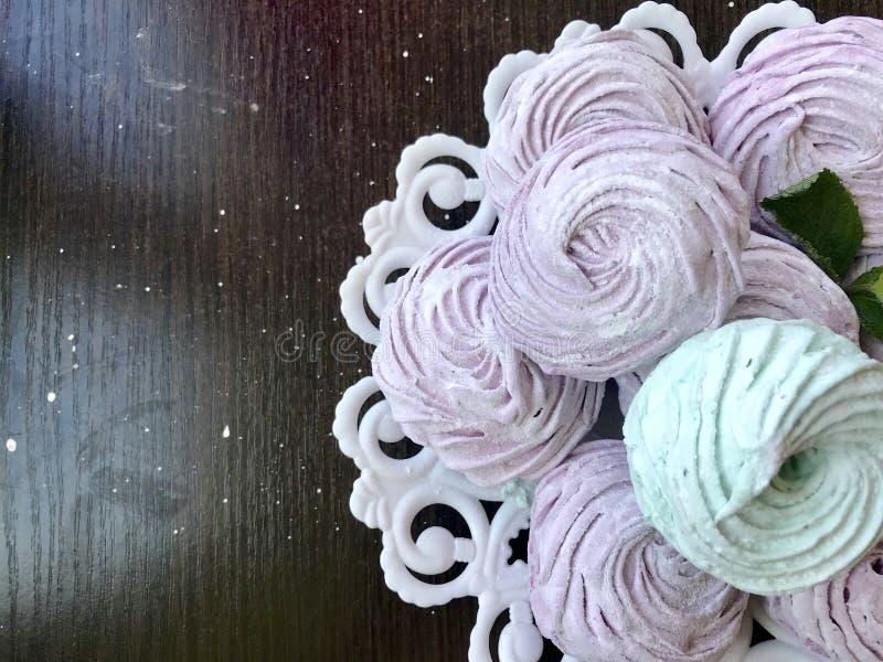 Hemlagade marshmallower lade p? en platta Dekorerat med mintkaramellsidor Marshmallow med en gr?splan och en rosa ton P? en m?rk  arkivbild