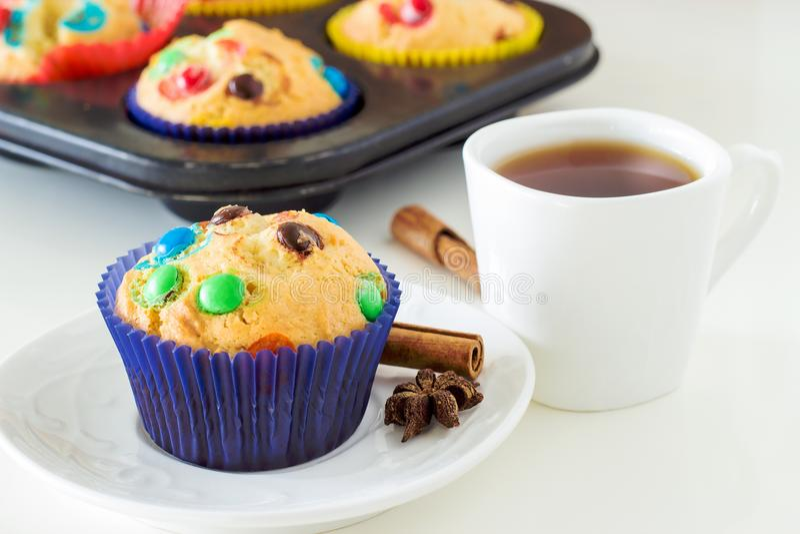 Hemlagade muffin med färgrika chokladchiper i mörker - fall för blått papper och en kopp av svart te Vit bakgrund Bekläda beskåda fotografering för bildbyråer