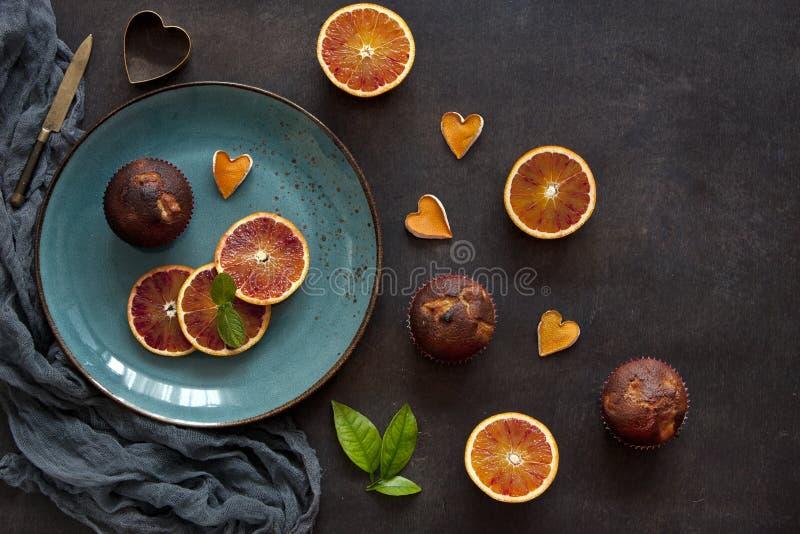 Hemlagade muffin och skivade apelsiner på tappningen träbakgrund royaltyfri fotografi
