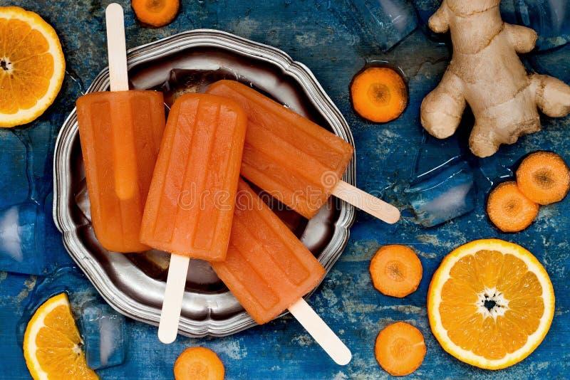 Hemlagade naturliga fruktsaftisglassar för apelsin och för morot med gurkmeja, honung och ingefäran fotografering för bildbyråer
