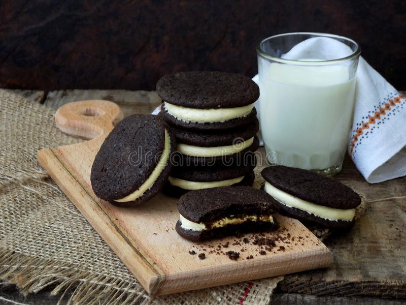 Hemlagade Oreo chokladkakor med vitt marshmallowkräm och exponeringsglas av mjölkar på mörk bakgrund arkivfoto