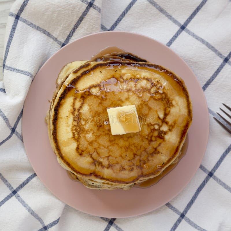 Hemlagade pannkakor med smör- och lönnsirap på en rosa platta, över huvudet sikt L?genhet som ?r lekmanna-, fr?n ?ver, b?sta sikt royaltyfri fotografi