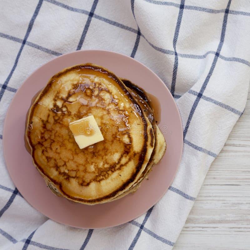 Hemlagade pannkakor med smör- och lönnsirap på en rosa platta, över huvudet sikt Lekmanna- l?genhet, b?sta sikt, fr?n ?ver arkivfoton