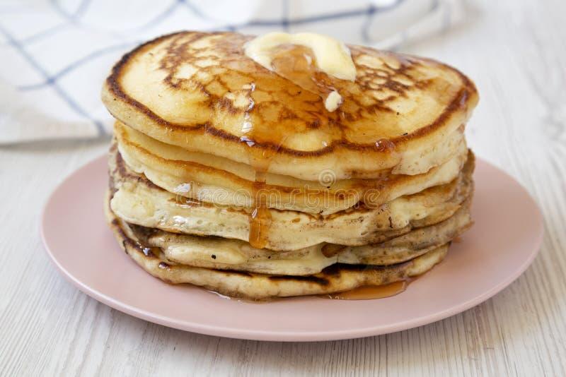 Hemlagade pannkakor med smör- och lönnsirap på en rosa platta, sidosikt N?rbild arkivbild