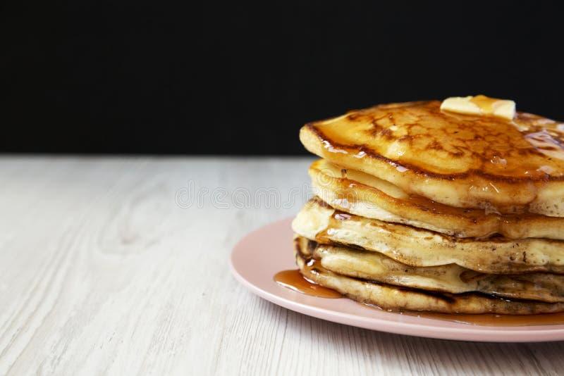 Hemlagade pannkakor med smör- och lönnsirap på en rosa platta, sidosikt N?rbild kopiera avst?nd arkivbild