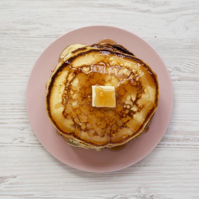 Hemlagade pannkakor med smör- och lönnsirap på en rosa platta på en vit träyttersida, bästa sikt ?ver huvudet plant l?gga, fr?n ? arkivbilder