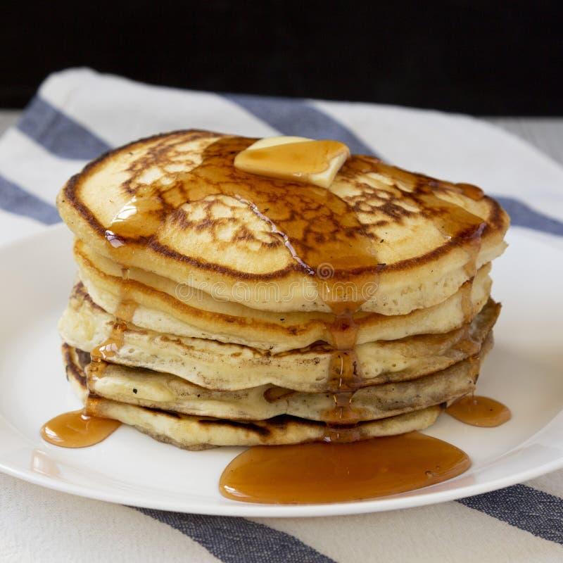 Hemlagade pannkakor med smör- och lönnsirap på en vit platta, sidosikt closeup royaltyfria bilder