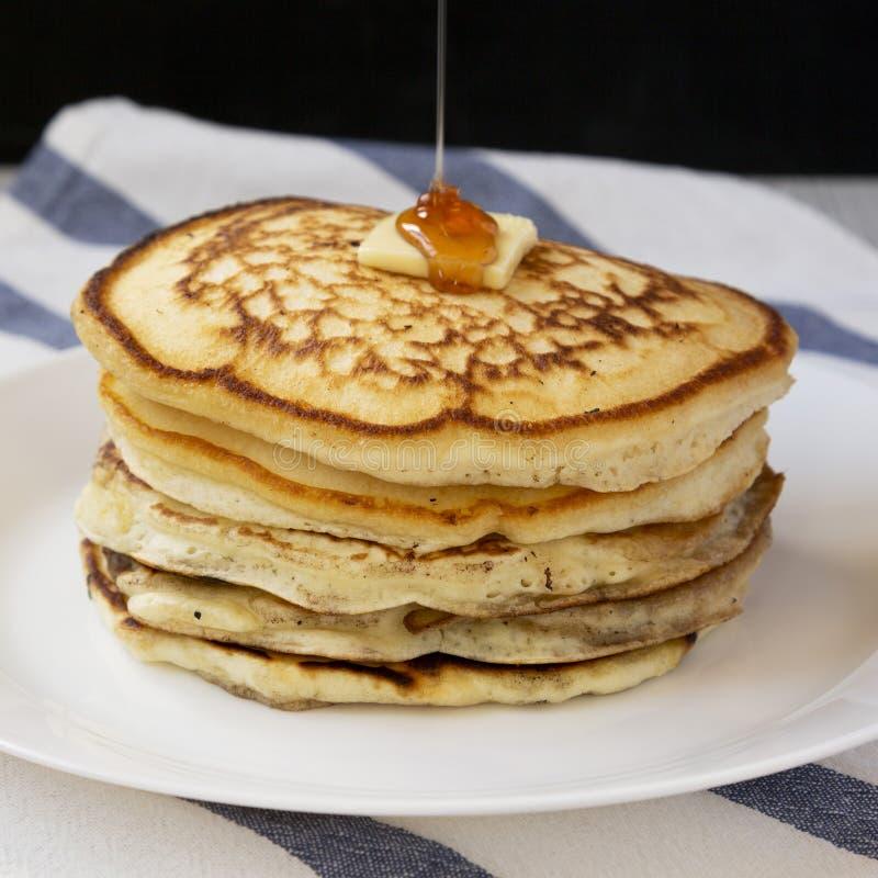 Hemlagade pannkakor med smör- och lönnsirap på en vit platta, sidosikt N?rbild arkivfoton