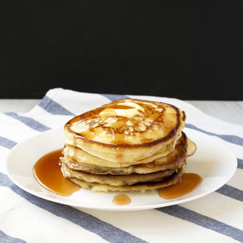 Hemlagade pannkakor med smör- och lönnsirap på en vit platta, sidosikt N?rbild royaltyfria foton