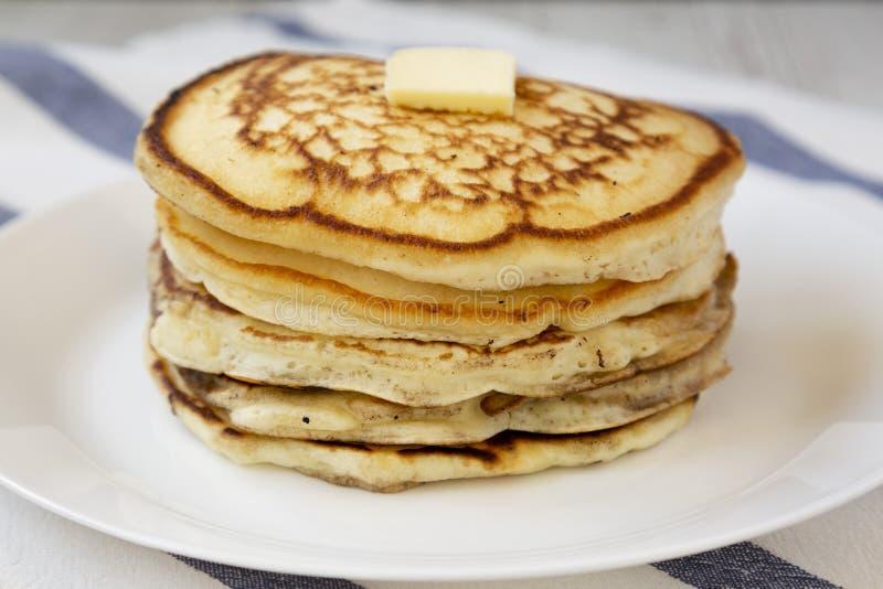 Hemlagade pannkakor med smör på en vit platta, sidosikt N?rbild arkivbilder